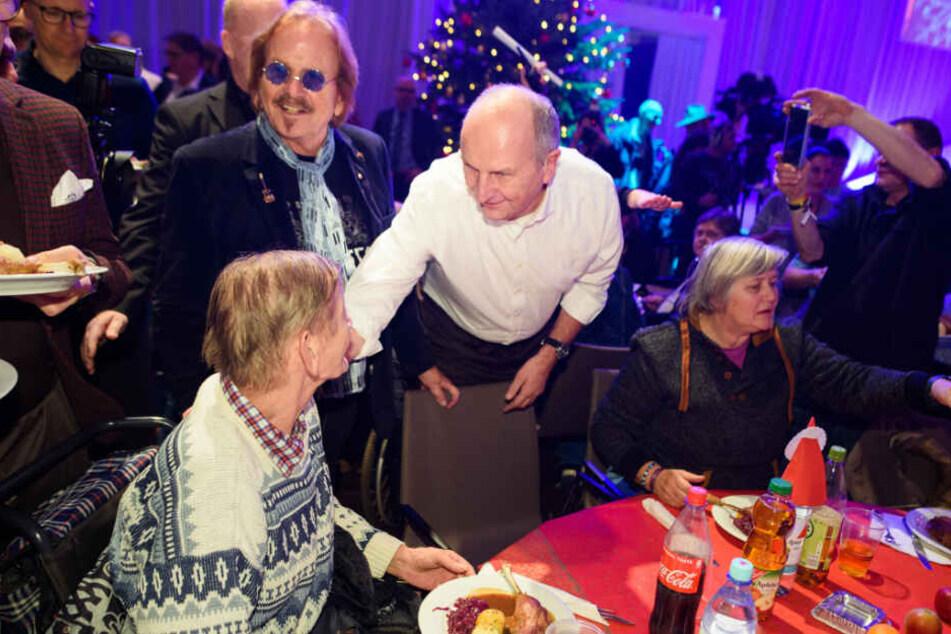 Musiker Frank Zander (l-r) und Dietmar Woidke (SPD), Ministerpräsident von Brandenburg, verteilen beim 25. Weihnachtsfest für Obdachlose und Bedürftige Weihnachtsgans an die Gäste.