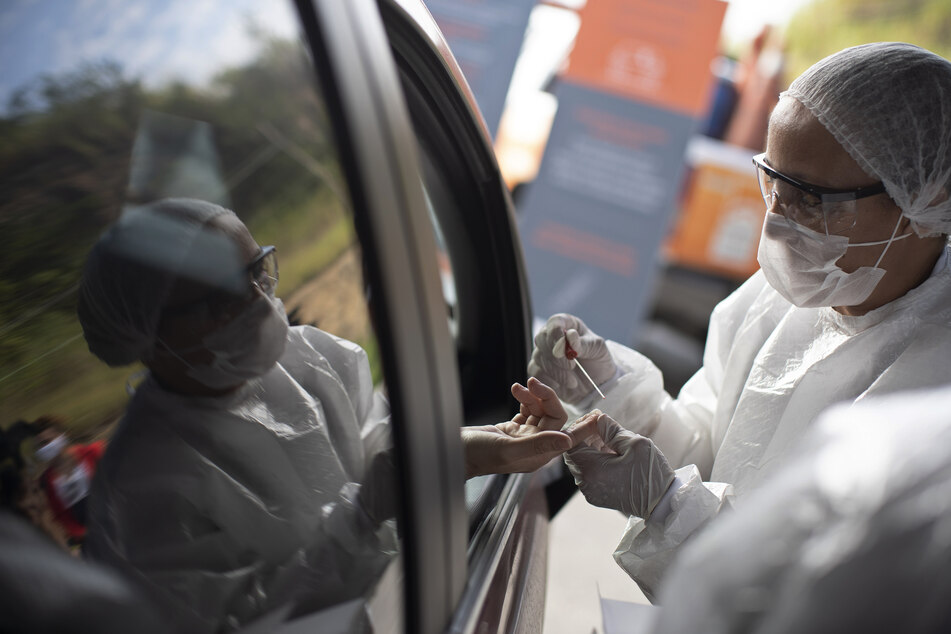Eine medizinische Mitarbeiterin entnimmt einer Person eine Blutprobe, um einen Corona-Test durchzuführen.