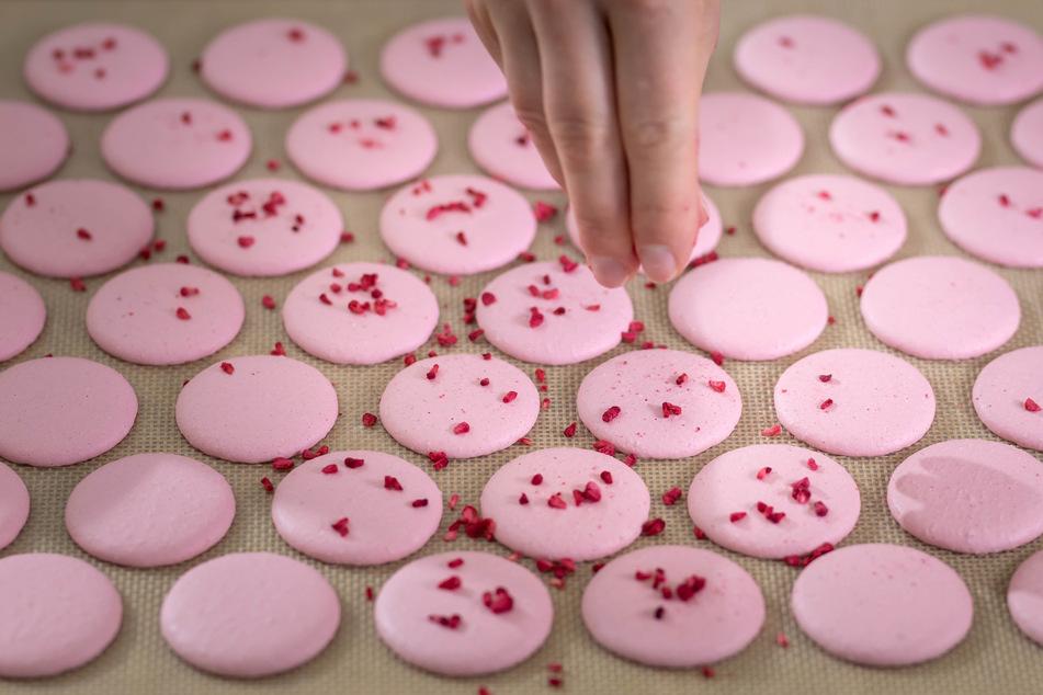 Macarons sehen einfach aus, aber die Herstellung verlangt Geduld, Fingerspitzen-Gefühl und Timing. Flamingo-farbene Makronen werden mit Streuseln verziert.