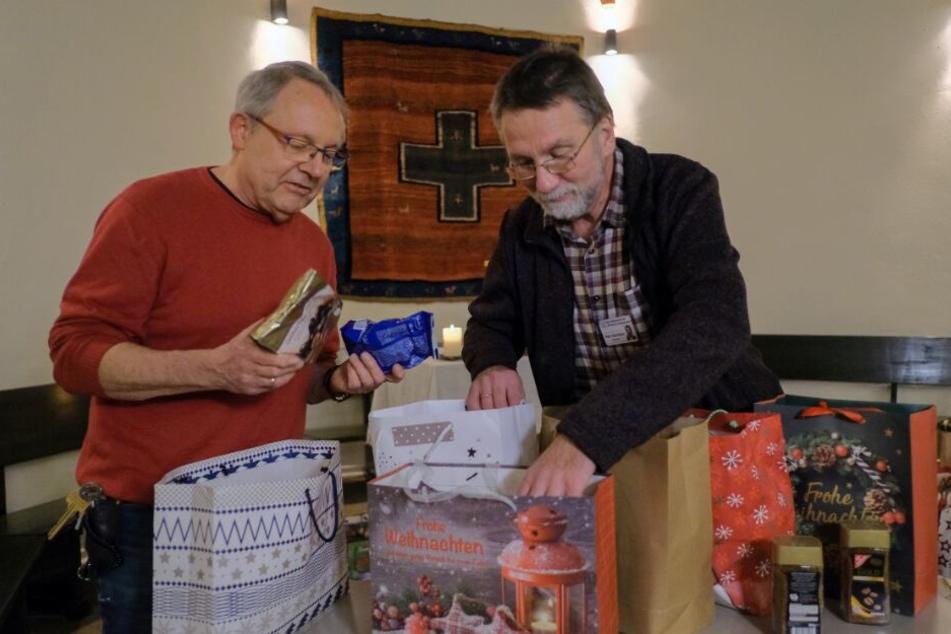 Der evangelische Gefängnispastor der Justizvollzugsanstalt Bremen, Peter Arenz (l), und sein katholischer Kollege Diakon Richard Goritzka packen gemeinsam Weihnachtstüten.