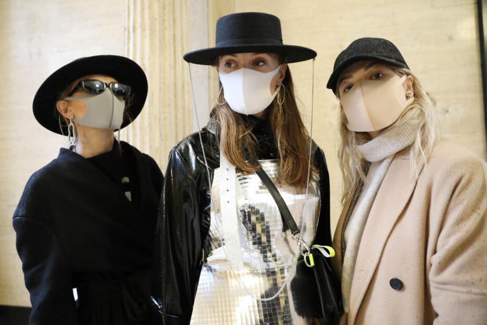 Besucher der Fashion Week aus Litauen tragen Gesichtsmasken und Kleidung der Modemarke kARTu während der London Fashion Week.