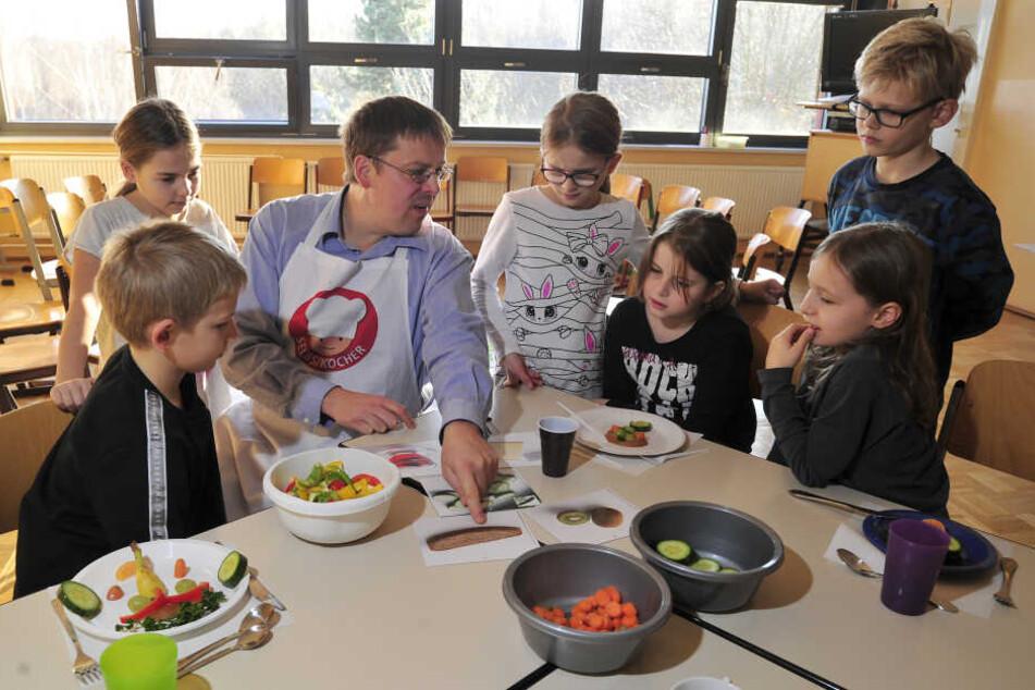 """Wulf Karl (44) vom Gesundheitsamt schnippelt mit Grundschülern der Charles-Darwin-Grundschule bunte Zutaten für eine """"gesunde Brotbüchse""""."""