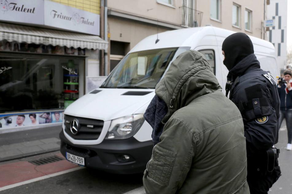 Ein Bundespolizist führt einen festgenommenen Mann zu einem Polizeifahrzeug.