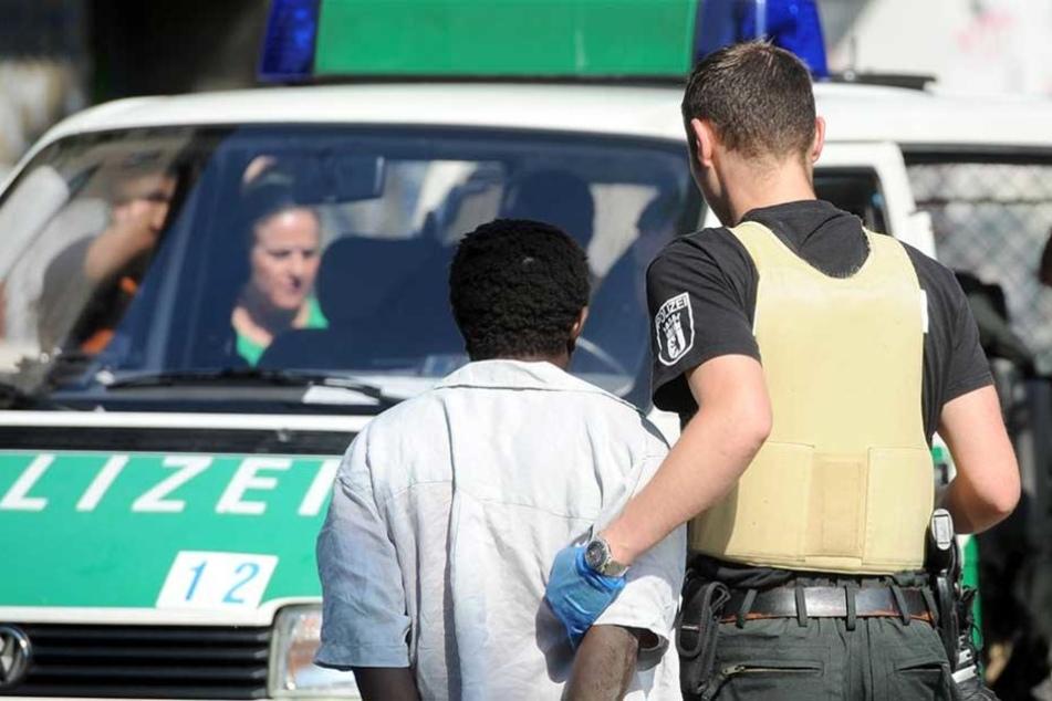 Ein Polizei hat während einer Razzia einen mutmaßlichen Drogendealer in Gewahrsam genommen..