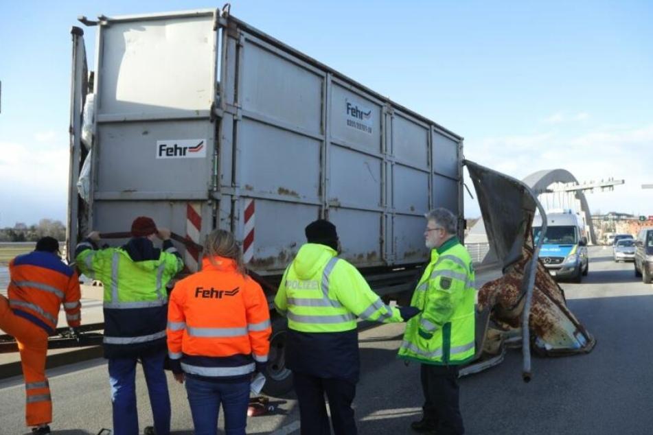 Die Bergung des LKW ist in vollem Gange. Durch den Unfall ist der hintere Container total verschoben, Müllsäcke quellen heraus.