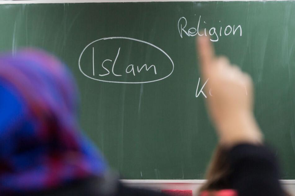 Eine Schülerin mit Kopftuch meldet sich an einer Schule bei einer Unterrichtsstunde zum Thema Islam.