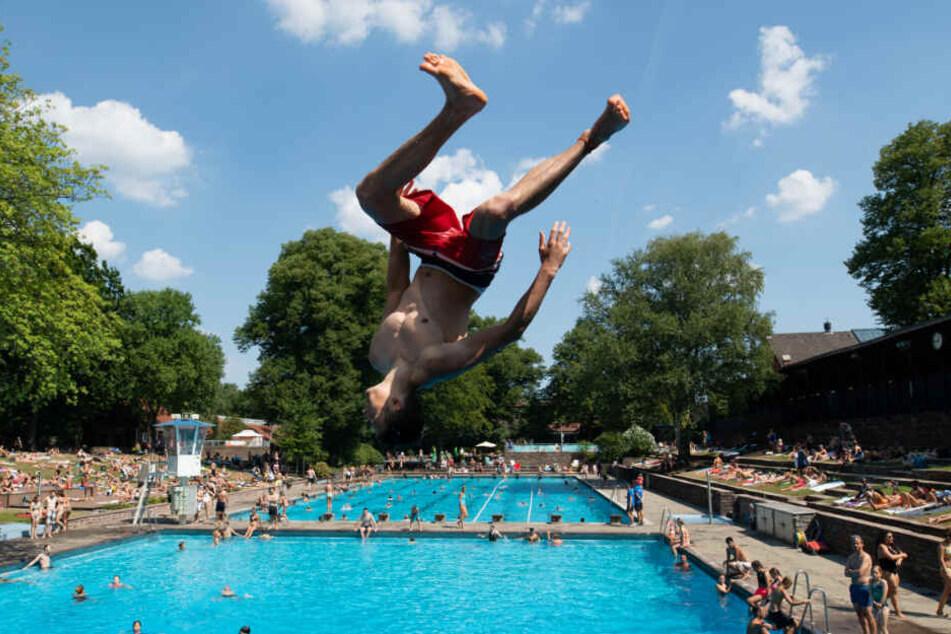 Ein Jugendlicher springt über Kopf vom Drei-Meter-Brett in das Becken.