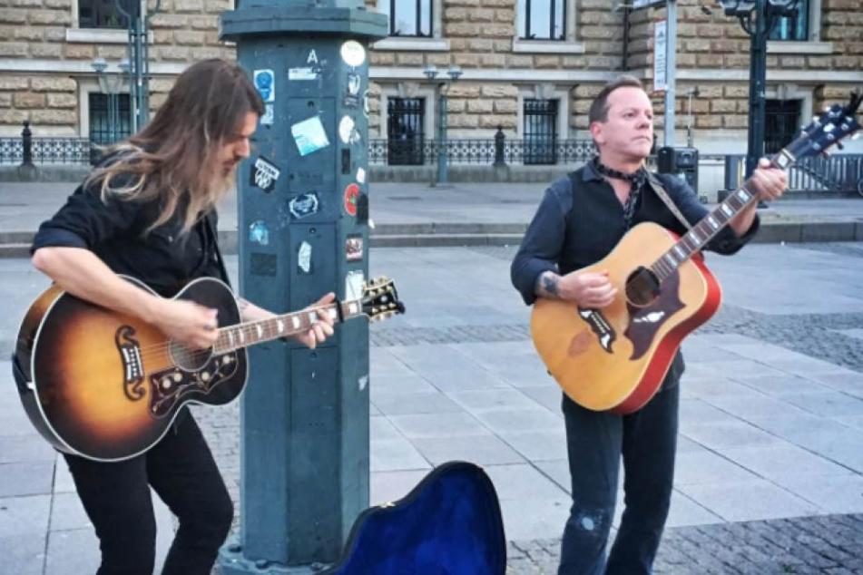 Kiefer Sutherland (51, r.) spielt an diesem Samstag als Straßenmusiker in Köln, kündigte er an.