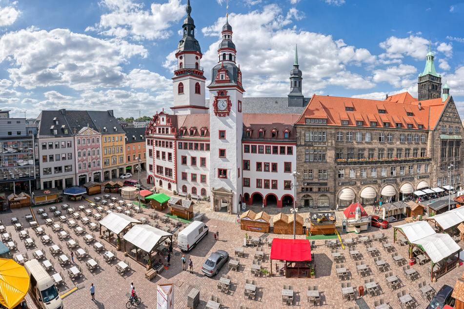 Tische und Stühle für das 31. Chemnitzer Weindorf stehen vor altem und neuem Rathaus in Reih und Glied.