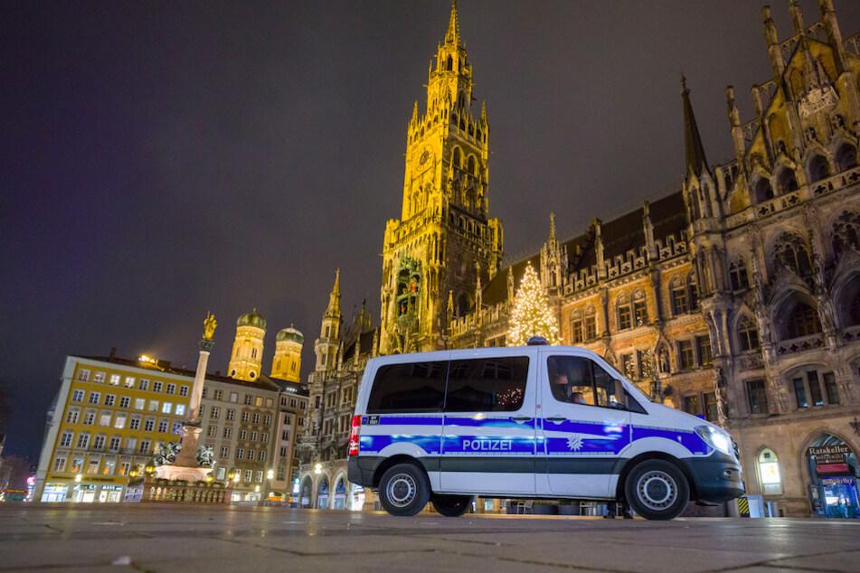 Ein Polizeiwagen fährt über den menschenleeren Marienplatz in München.