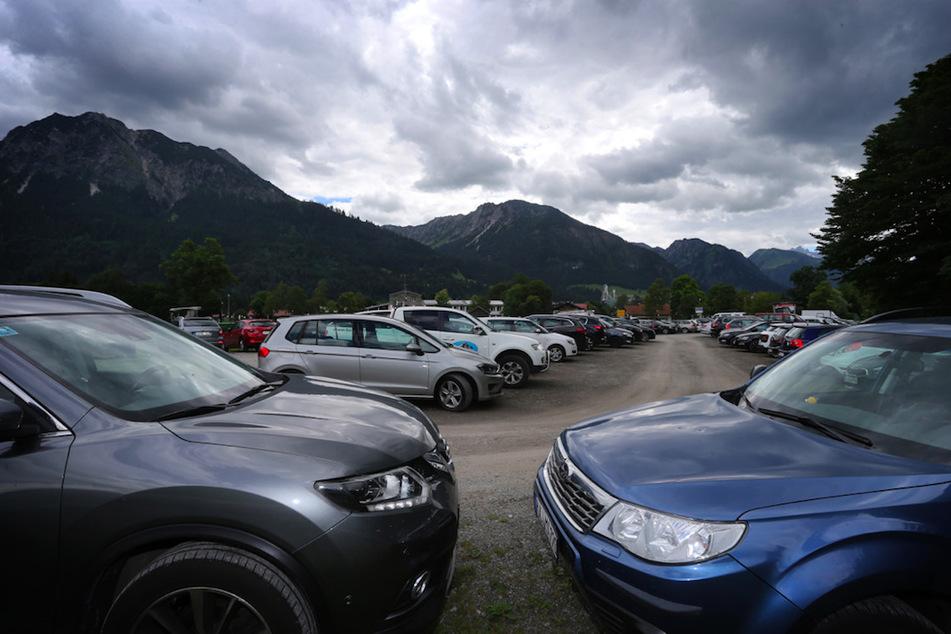 Autos von Ausflüglern stehen am Ortseingang von Oberstdorf auf einem Parkplatz.