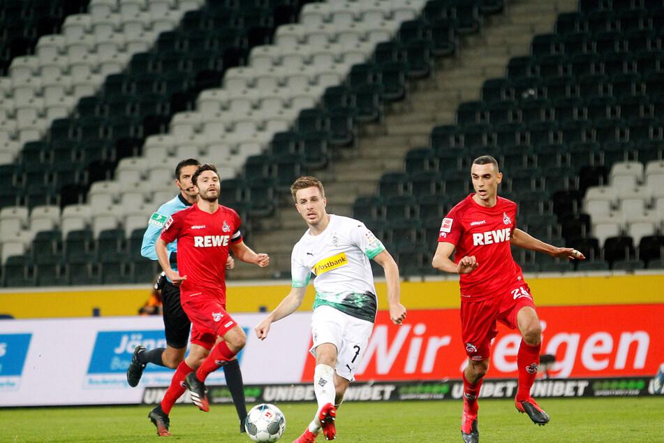 Der Mönchengladbacher Patrick Herrmann (M) und die Kölner Jonas Hector (l) und Ellyes Skhiri kämpfen um den Ball.