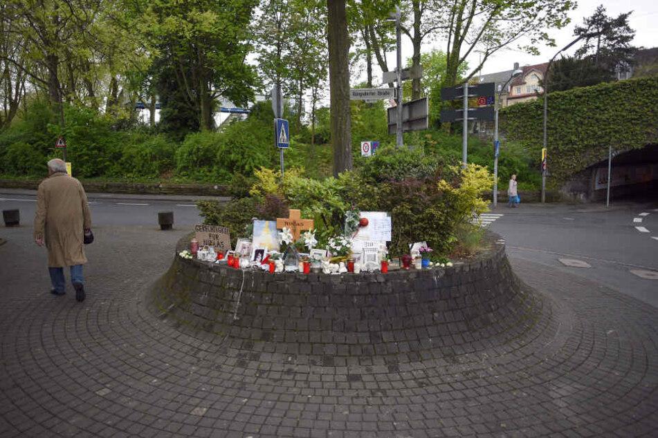 Schilder, Blumen und Kerzen stehen am 4.5.2017 in Bonn-Bad Godesberg neben einem Holzkreuz an der Stelle, an der der später verstorbene Niklas P. am 7.5.2016 von Schlägern attackiert wurde.