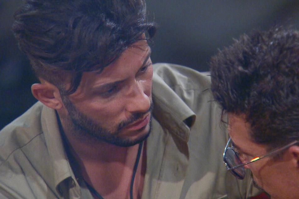Am Lagerfeuer bringt Domenico (l.) Nataschas Ex, Umut Kekilli, ins Spiel. Er soll was mit Evelyn gehabt haben. Chris ist erstaunt.