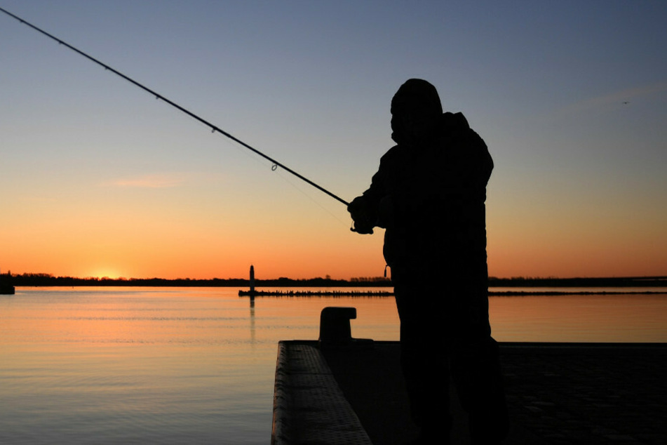 Die Silhouette eines Anglers im Licht der aufgehenden Sonne. Die Corona-Pandemie hat in Brandenburg einen Angelboom ausgelöst. (Symbolfoto)