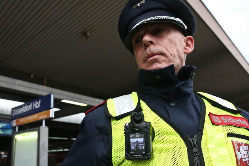 An der Weste eines Sicherheitsmitarbeiters der Deutschen Bahn hängt eine Bodycam.