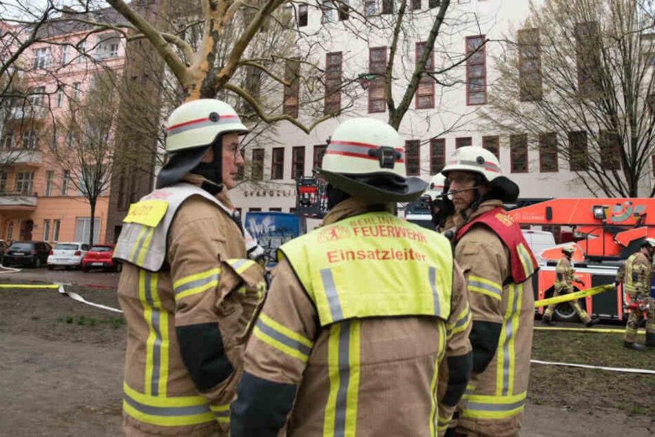 Einsatzkräfte stehen vor dem Haus, wo es zu einem Wohnungsbrand kam.
