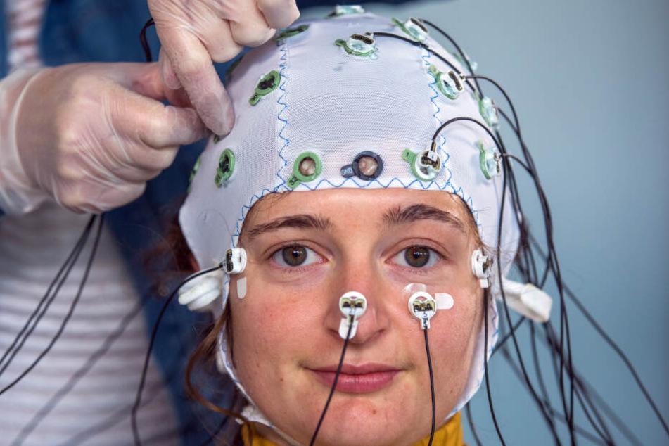 Eine Probandin trägt eine Haube mit Elektroden zur Messung der Hirnströme. (Symbolbild)