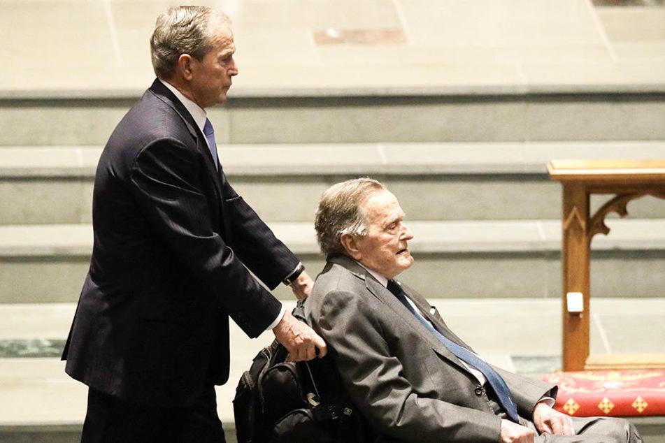 George H.W. Bush (re.) wird von seinem Sohn George W. Bush im Rollstuhl geschoben.