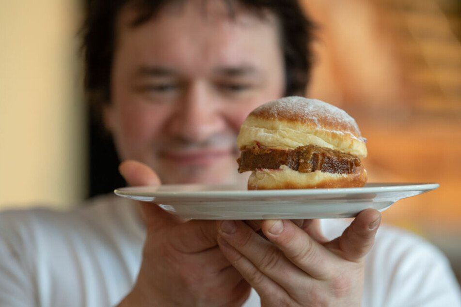 Bäckermeister Florian Perkmann hält einen Krapfen, der mit Leberkäse und süßem Senf belegt wurde in der Hand.