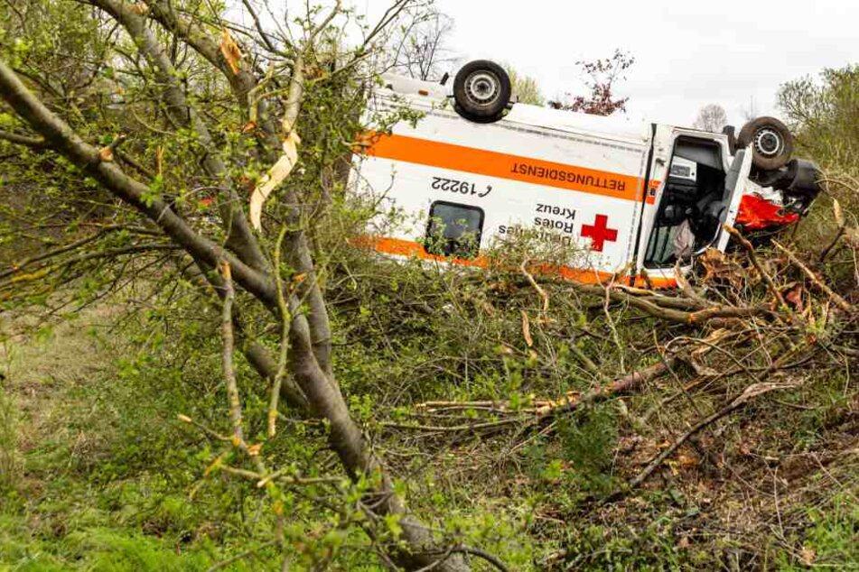 Der Rettungswagen liegt kopfüber in einer Böschung.