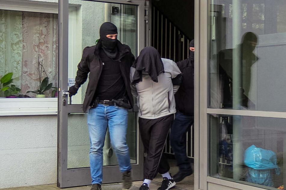 Der Tatverdächtige wird von zwei vermummten Beamten aus dem Haus geführt.