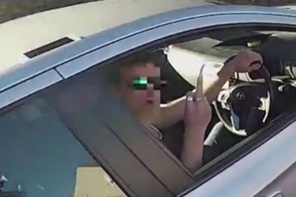 Statt dem Biker dankbar zu sein, zeigt der Autofahrer im noch den Mittelfinger.