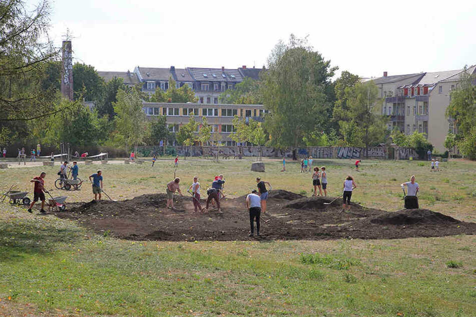 Subbotnik auf dem Russensportplatz: Rund 35 Helfer verteilten die aufgeschüttete Erde auf dem Boden.