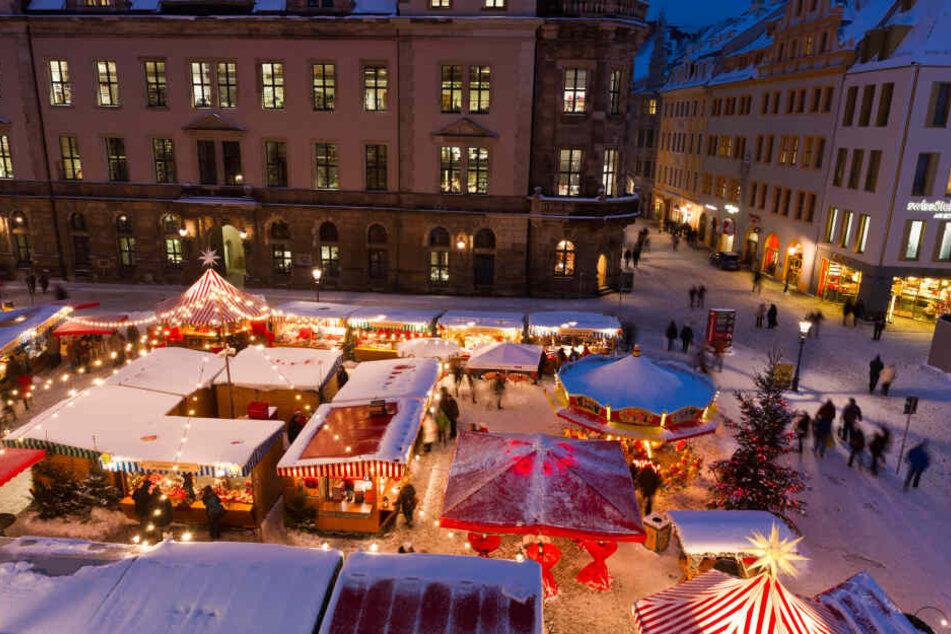 Der altertümlich gestaltete Weihnachtmarkt am Dresdner Schloss grenzt an eine Eisbahn.