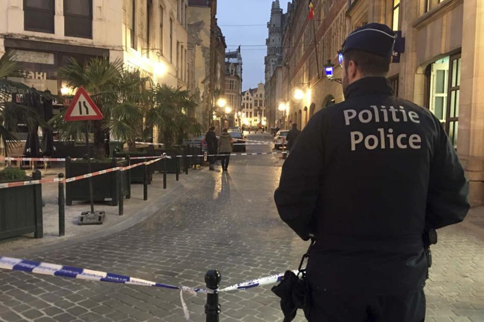 Ein Polizist steht hinter einem Polizeiband während der Ermittlungen am Ort einer Messerattacke im Zentrum von Brüssel.