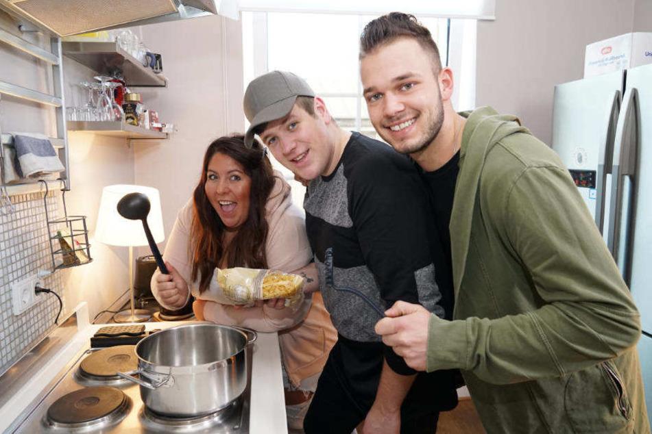 Janina, Lukas und Michael (l-r) haben Spaß beim gemeinsamen Kochen.