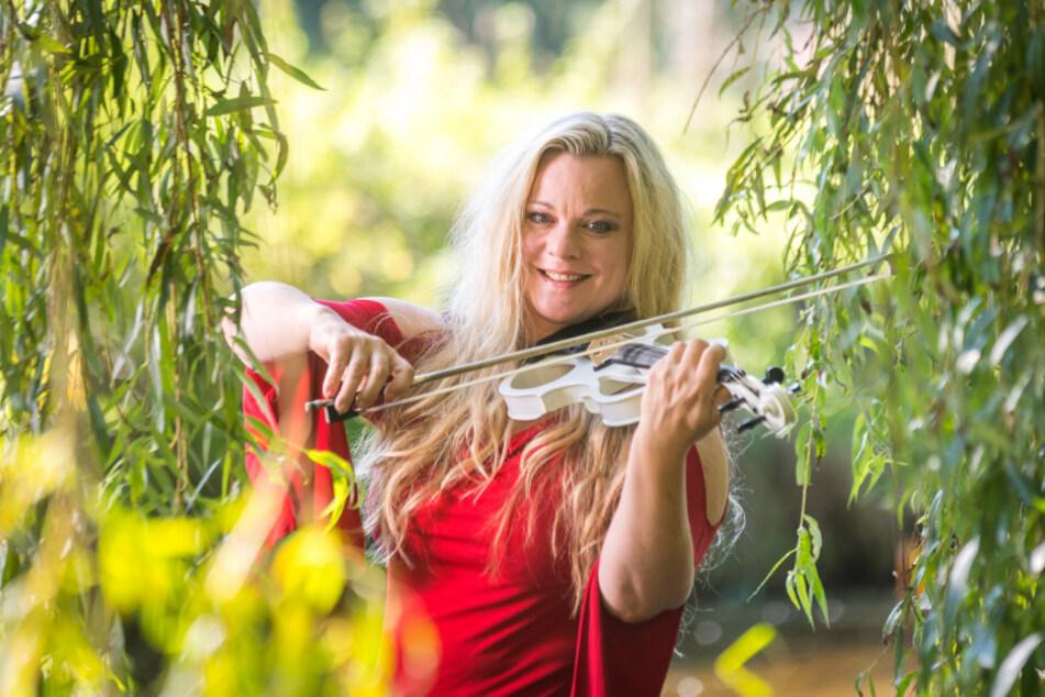 Unter der alten Weide spielt Katrin Wettin (46) Geige - mit den Füßen im Wasser.