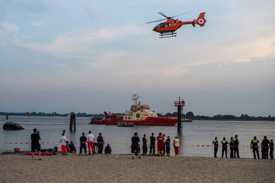 Ein Hubschrauber sowie mehrere Boote suchen in der Elbe nach dem Vermissten.