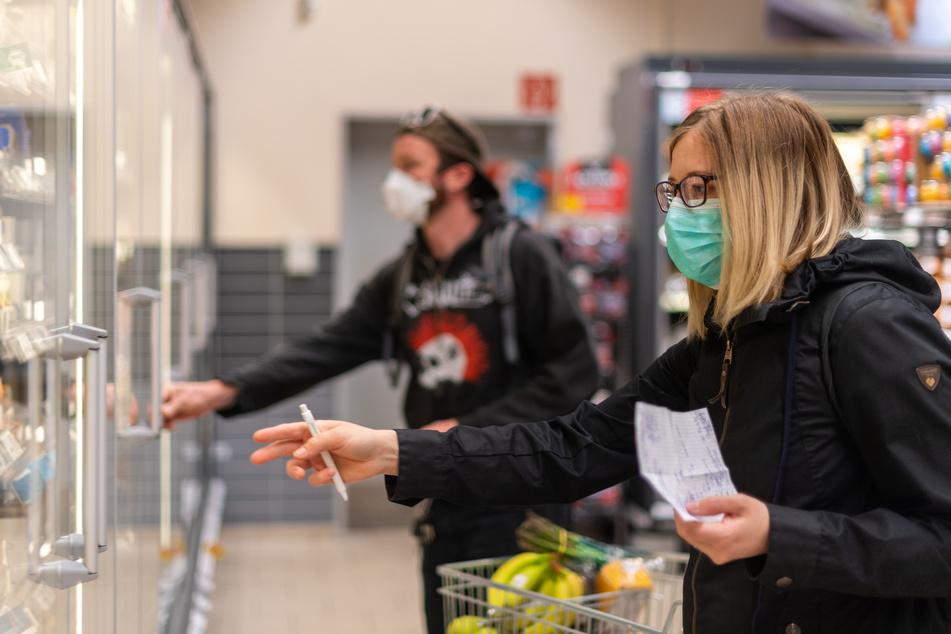 Kunden gehen in einem Supermarkt einkaufen und tragen dabei Mundschutz.