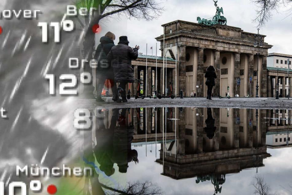 Das Brandenburger Tor spiegelt sich in einer Regenpfütze.