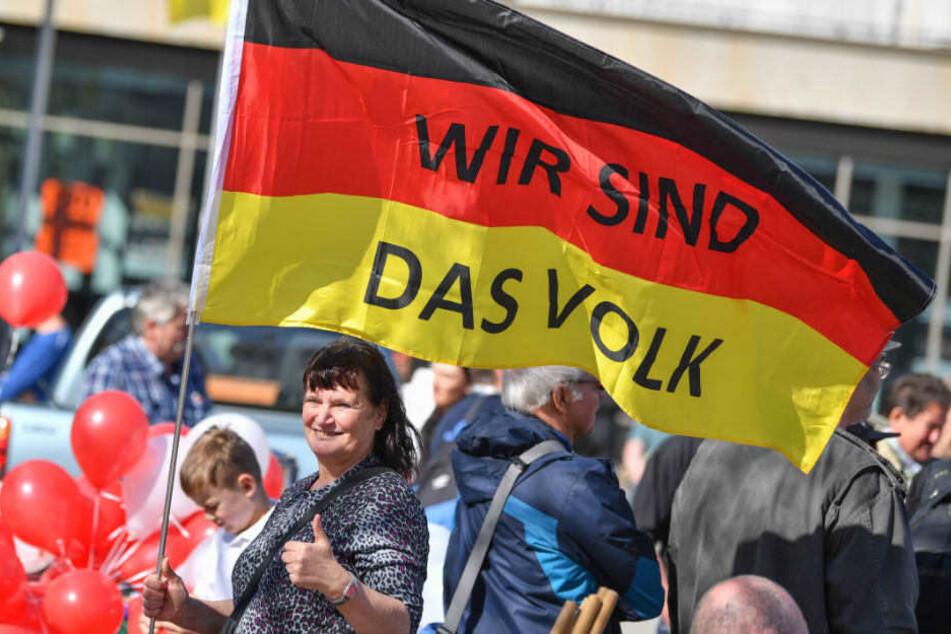 """Eine Demonstrantin hält eine Deutschlandfahne mit der Aufschrift """"Wir sind das Volk""""."""