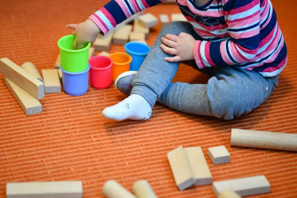 Ein Mädchen spielt in einer Kita mit bunten Bechern und Bauklötzen.