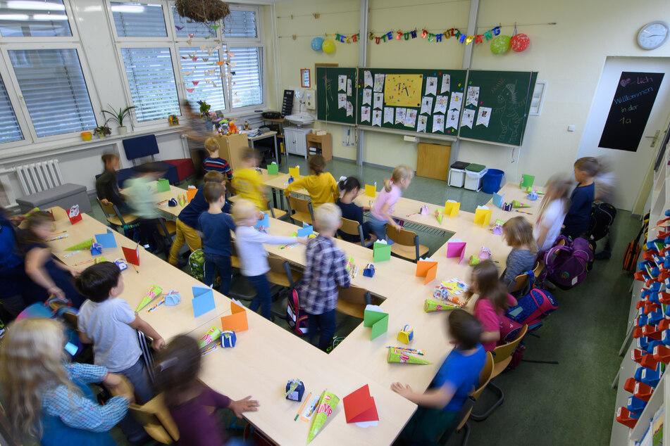 Grundschüler einer ersten Klasse setzen sich auf die Plätze in ihrem Klassenzimmer.