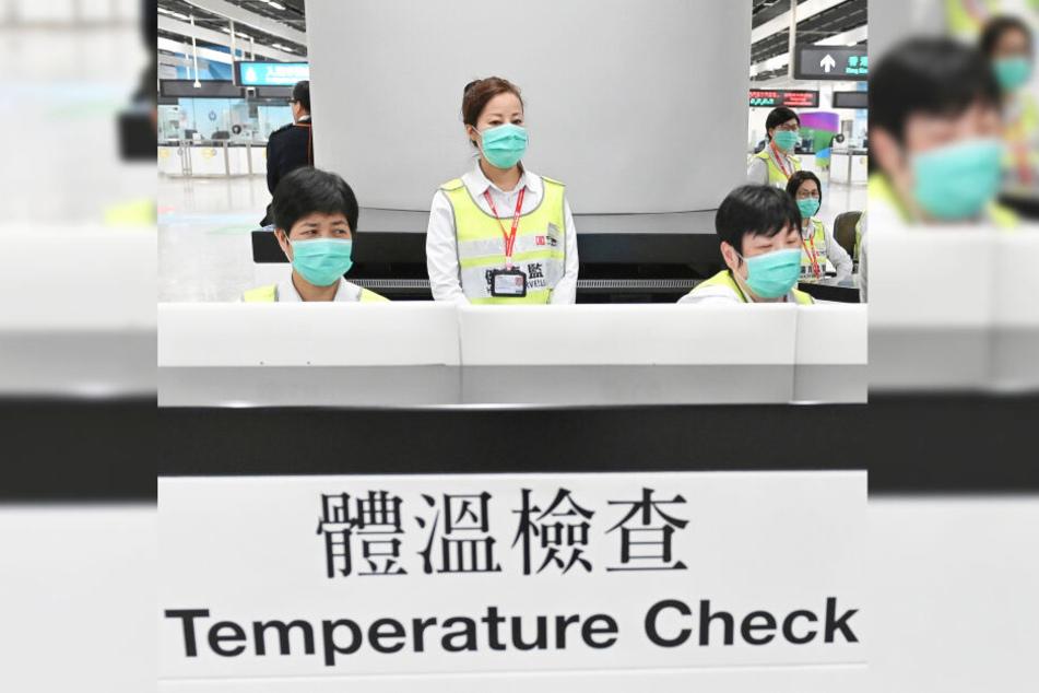 Mitarbeiter des Honkonger Gesundheitswesens kontrollieren Reisende.