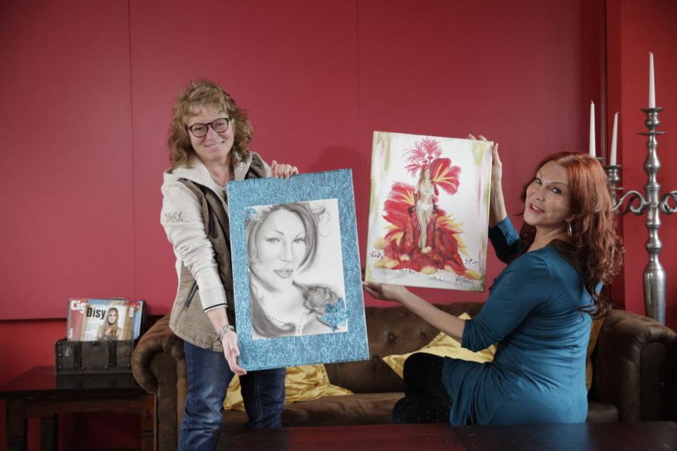 Katarina Mergen (46, l.) überreicht Zora Schwarz ihre beiden Bilder.