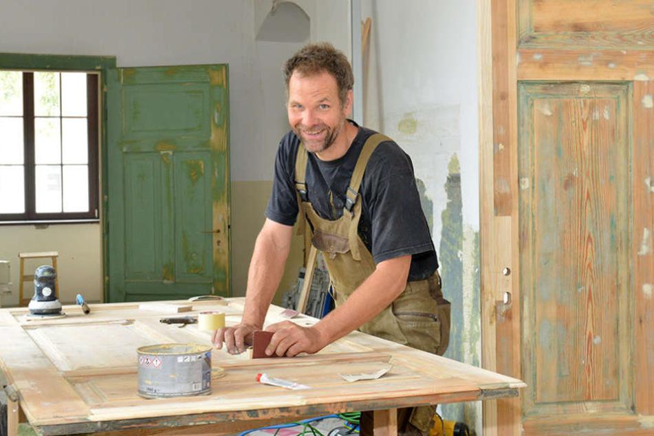 Tischler Voud Jansen (44) arbeitet im Gymnasium Dreikönigskirche die  Originaltüren wieder auf.
