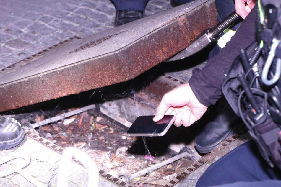 Ein Polizist hebt das Smartphone auf, das tatsächlich unter dem schweren Deckel zum Vorschein gekommen ist.