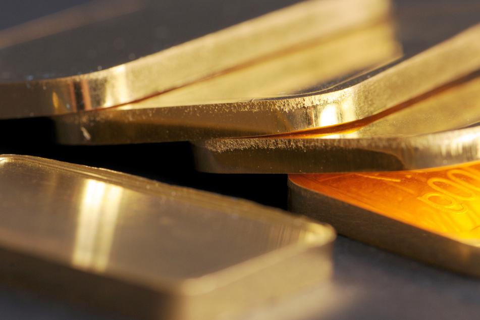 Goldbarren mit 100 Gramm Gewicht liegen auf einem Tisch.