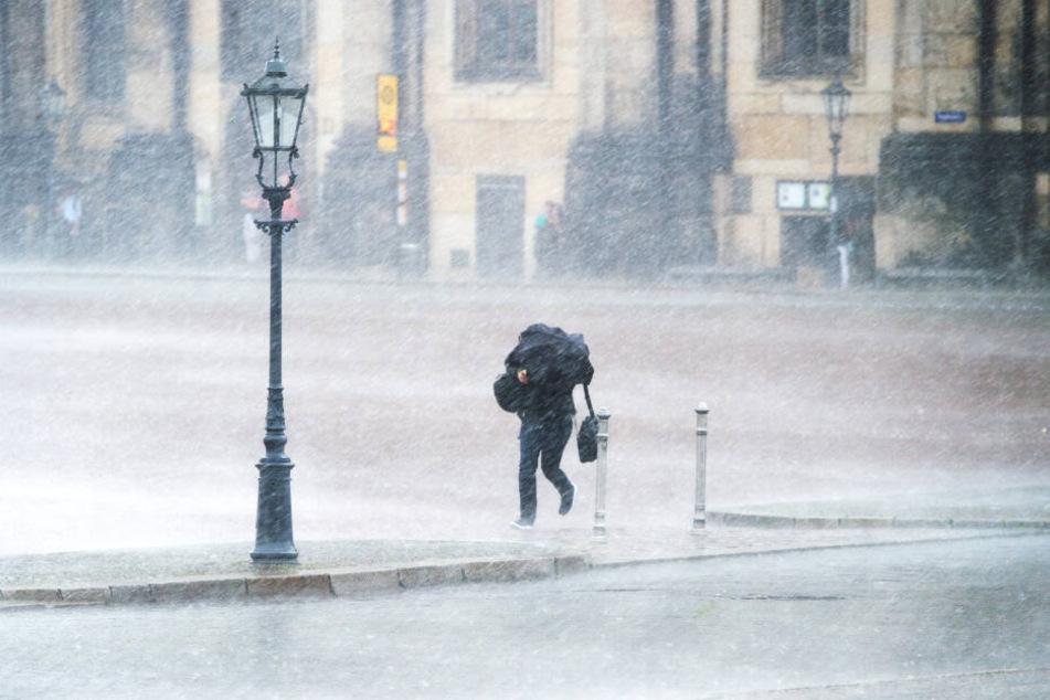 Ein Passant kämpft auf dem Theaterplatz gegen Sturm und Regen an.