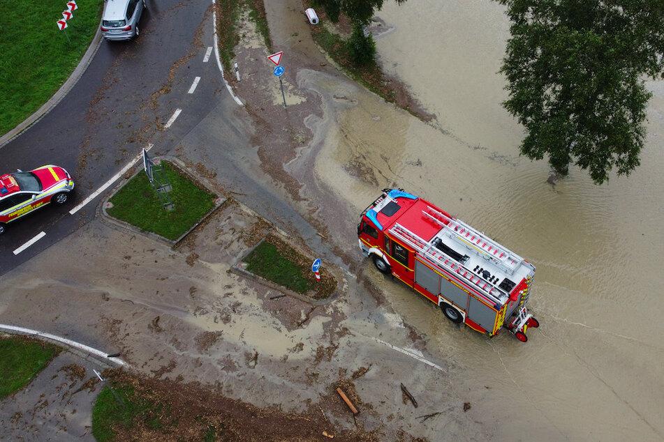 Ein Feuerwehrfahrzeug fährt durch das hoch stehende Wasser an einem Kreisverkehr vor Rettenberg.