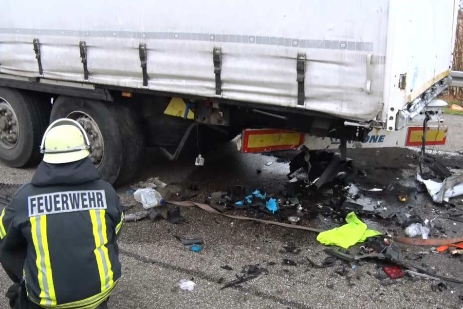 Ein Feuerwehrmann kniet neben dem Lastwagen.