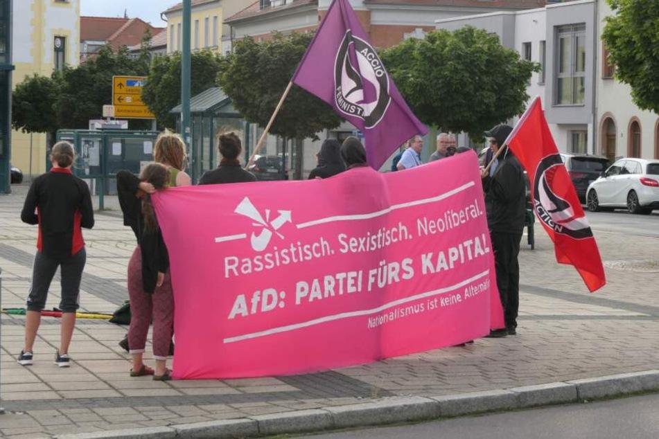 Ein kleiner Protestzug hat sich vor dem Veranstaltungsort gebildet.