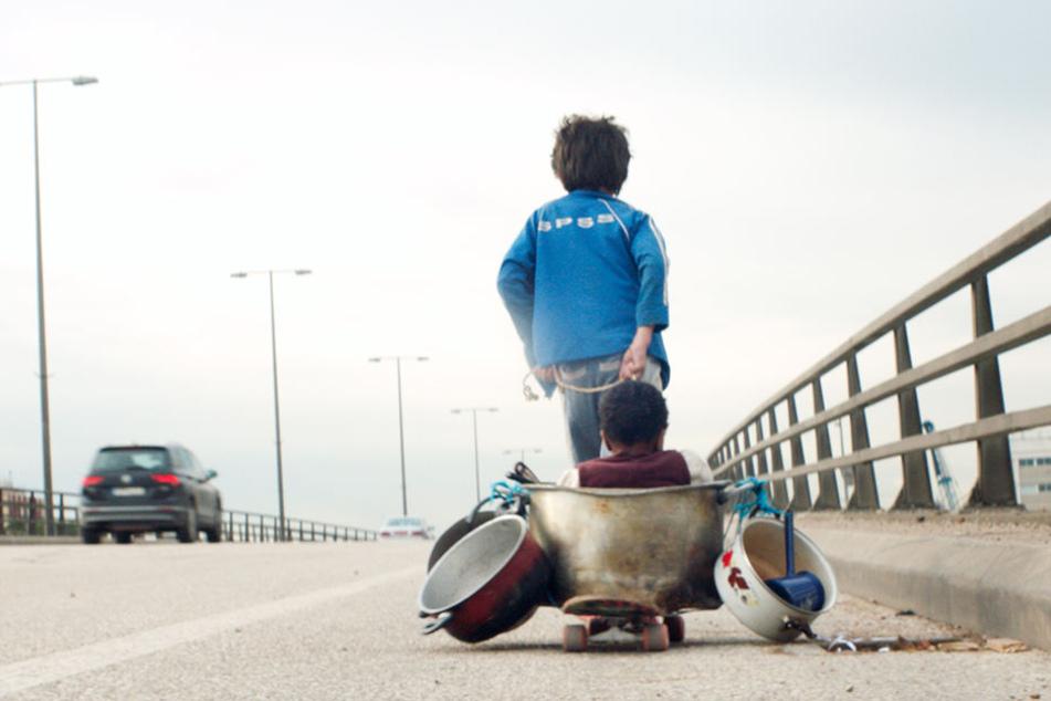 Zain (Zain Al Rafeea) zieht den improvisierten Kinderwagen mit Yonas (Boluwatife Treasure Bankole) am Seitenstreifen der Stadt-Autobahn Beiruts entlang.