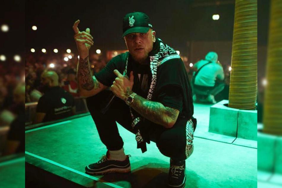Rapper Bonez MC zeigt sich auf der Bühne mit einer Waffen-Bewegung.