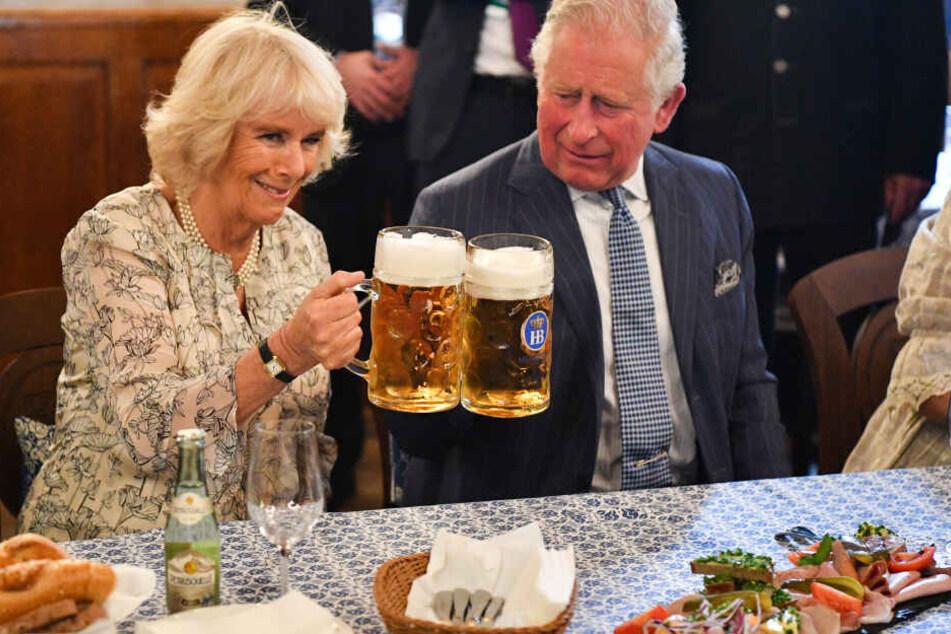 Der britische Thronfolger Prinz Charles und seine Ehefrau Camilla stoßen mit Maßkrügen an im Hofbräuhaus.